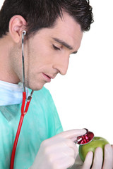 Doctor using stethoscope on an apple