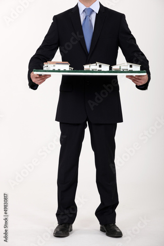Businessman holding a model of a housing estate