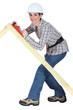 Tradeswoman using a plane to smooth a wooden frame