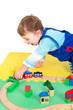 Kleinkind spielt mit Holzeisenbahn