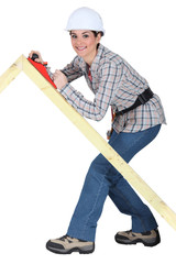 Tradeswoman using a plane to smooth a wooden frame