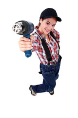 Tradeswoman holding up a heat gun