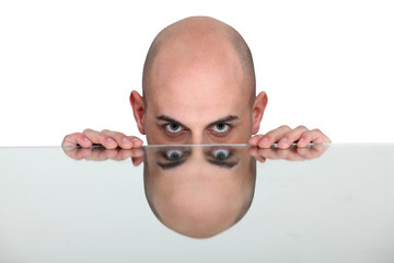 Bald man resting head on reflective surface