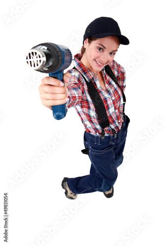 Tradeswoman holding up a heat gun