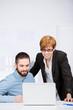zwei junge kollegen schauen auf laptop