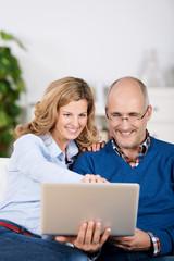 lachendes paar schaut auf laptop