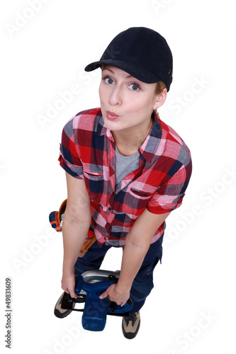 Blond worker struggling to carry circular saw