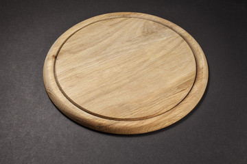 round wooden breadboard isolated on grey background