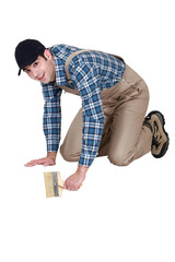 craftsman painter working on his knees