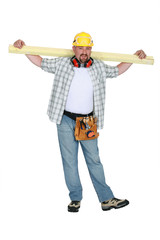 A carpenter holding a plank.