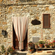 doorway to the tuscan house with striped outdoor curtain