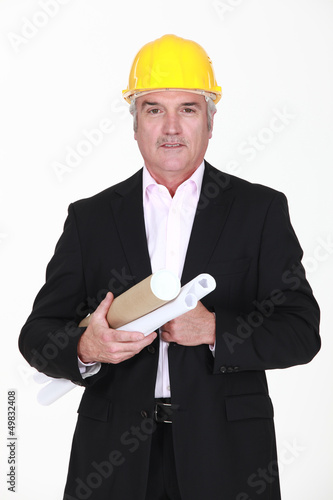 Senior architect carrying plans
