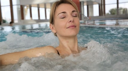 Woman enjoying bath in spa center