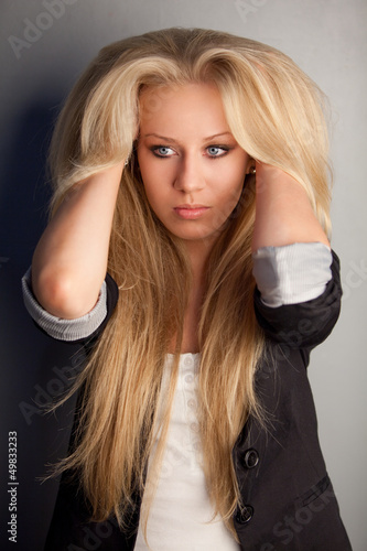 Serious blonde launched her hands under her hair