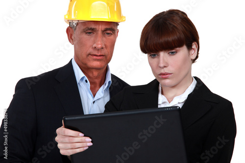 Architect showing document to assistant