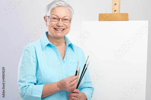 Old lady with paintbrush and canvas