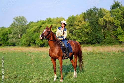 pretty young cowgirl riding horse