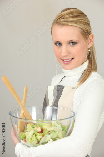 Woman carrying bowl of salad on white background