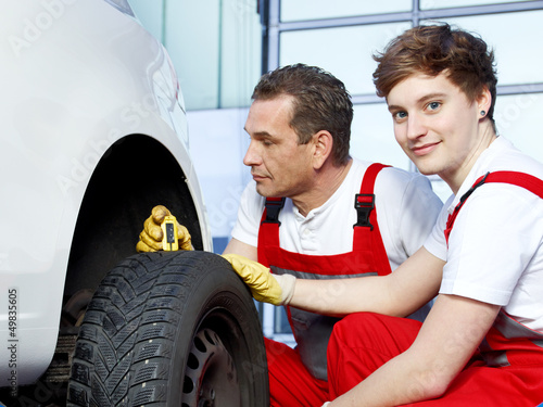 Mechanics and trainee check the tread pattern of a tire