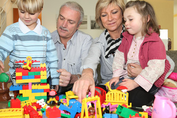 grandparents playing with grandchildren playing legos