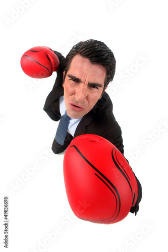 businessman holding boxing gloves looking ferocious