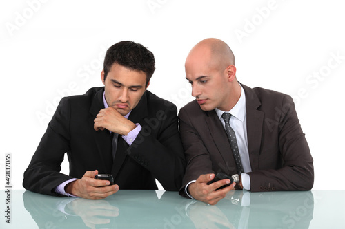 Businessmen comparing phones
