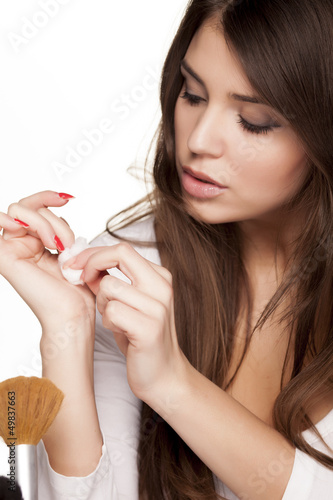 woman  using a cotton to removes her nail polish from her nails