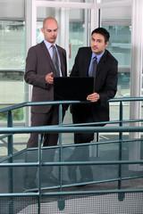 Businessmen, using laptop on hall