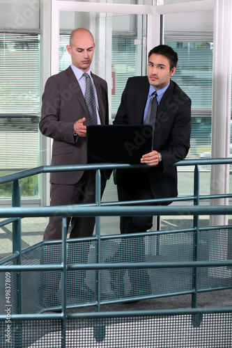 Businessmen, using laptop on hall