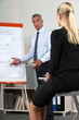 Businessman giving presentation with aid of flip-chart