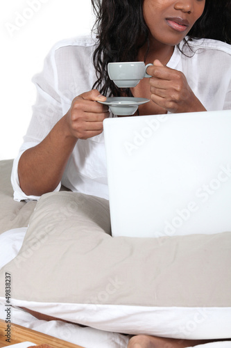 African woman drinking her coffee in bed