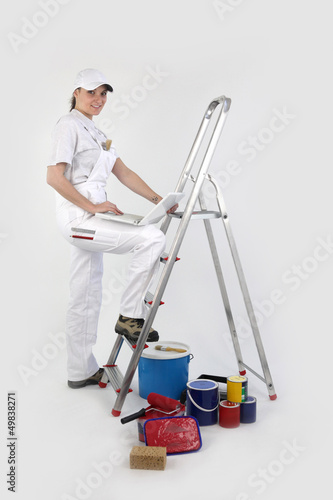 female painter on a ladder