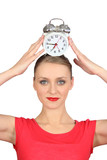 Smiling woman  putting alarm clock on her head