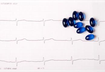 Blue pills on ECG chart (electrocardiogram)