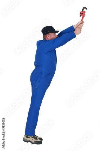 Plumber with wrench reaching upwards