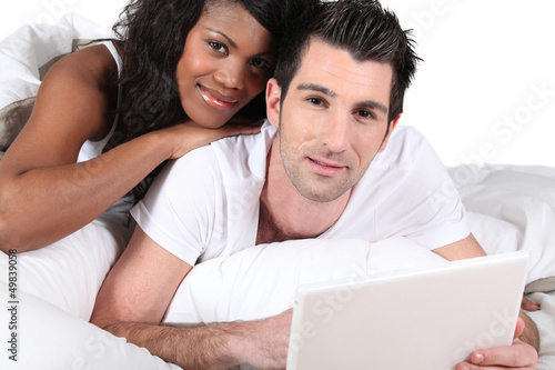 Mixed-race couple using laptop at home