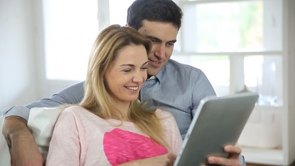 Couple websurfing on internet with tablet