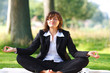 businesswoman meditating outdoor in park