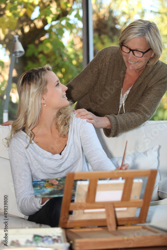 Woman encouraging a young painter at home