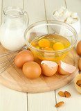 Broken egg in bowl and various ingredients next to them