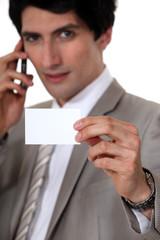 handsome businessman showing business card