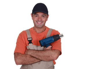 A male construction worker with a hot air blower.