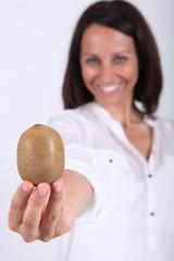 Woman holding a kiwi