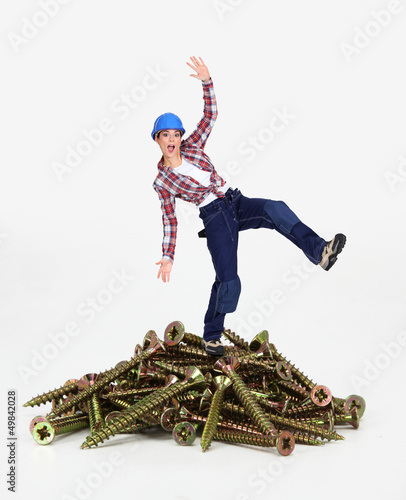 Woman balancing on pile of screws