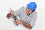 Tradesman clasping a chisel with a pair of pliers