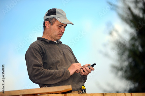 Carpenter sending text message whilst working outdoors
