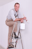 Man posing with paint brush whilst up ladder