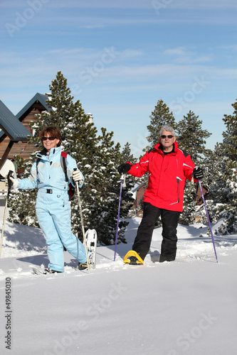 Mature couple walking in snow shoes