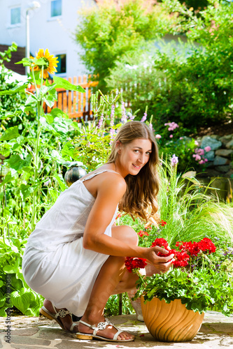 Woman looking at her flowers in the garden