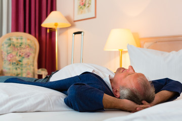Älterer Mann liegt auf dem Bett im Hotelzimmer
